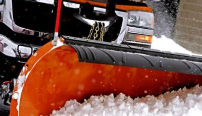 orange snow plow removing snow